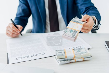 Photo for Cropped view of man holding money while signing contract - Royalty Free Image