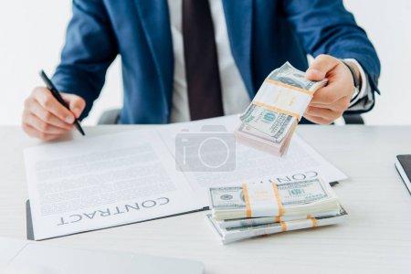 Photo pour Vue recadrée de l'homme retenant l'argent tout en signant le contrat - image libre de droit