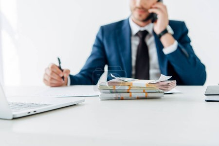 selective focus of money near man talking on smartphone in office