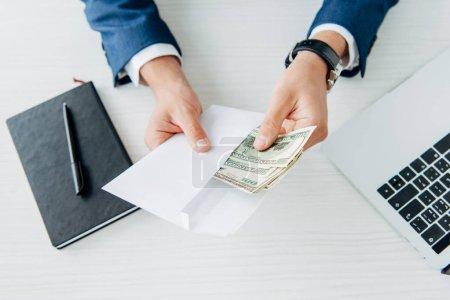 Photo for Top view of man holding envelope with money near laptop on table - Royalty Free Image