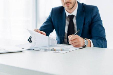 Photo pour Vue recadrée de l'homme d'affaires retenant le document près du pot-de-vin - image libre de droit
