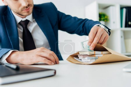 selective focus of businessman touching money in envelope on table