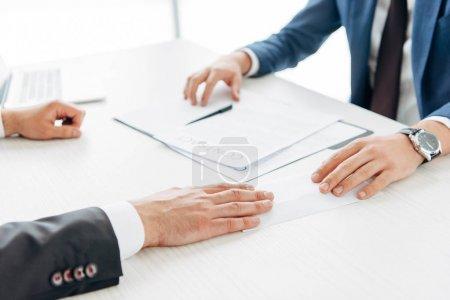 Photo pour Vue recadrée des hommes d'affaires près du contrat et de la plume sur la table - image libre de droit