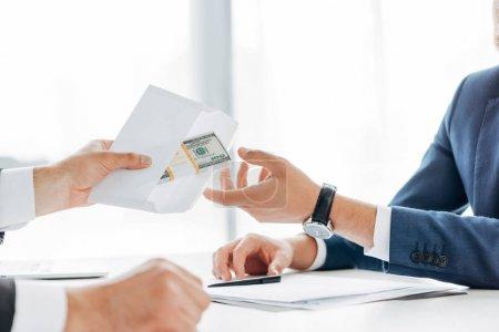 Photo pour Vue recadrée de l'homme donnant enveloppe avec de l'argent au partenaire d'affaires - image libre de droit
