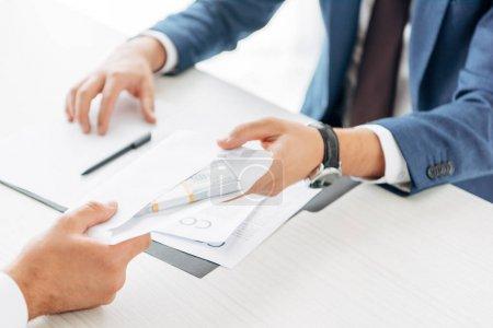 Photo pour Vue recadrée de l'homme d'affaires donnant l'enveloppe avec l'argent au associé d'affaires - image libre de droit