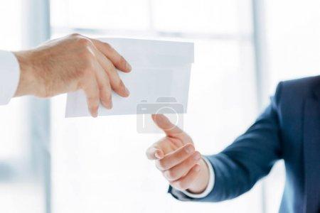 Photo pour Vue recadrée de l'homme d'affaires donnant enveloppe blanche avec pot de vin à un partenaire d'affaires dans le bureau - image libre de droit
