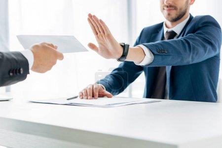 Photo pour Vue recadrée de l'homme geste près partenaire d'affaires donnant enveloppe avec pot de vin dans le bureau - image libre de droit