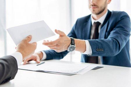 Photo pour Vue recadrée de l'homme donnant enveloppe avec pot de vin à un partenaire d'affaires près de la table - image libre de droit