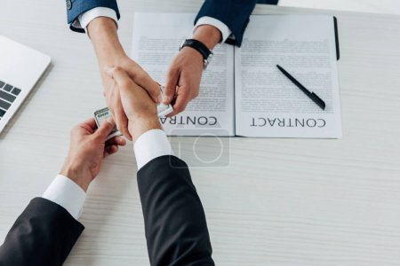 top view of man giving money and shaking hands with business partner