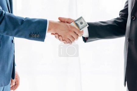 Photo pour Vue recadrée de l'homme donnant pot de vin à un partenaire d'affaires et serrant la main sur blanc - image libre de droit