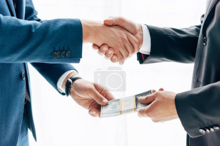 Photo pour Vue recadrée de l'homme d'affaires donnant le pot-de-vin à l'associé d'affaires et se serrant la main sur le blanc - image libre de droit