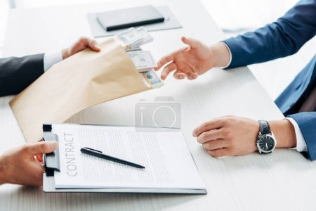 Photo for Cropped view of man taking envelope with cash near business partner holding clipboard and contract - Royalty Free Image