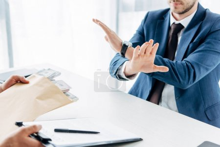Photo for Cropped view of businessman gesturing near business partner giving envelope with money and clipboard with contract in office - Royalty Free Image