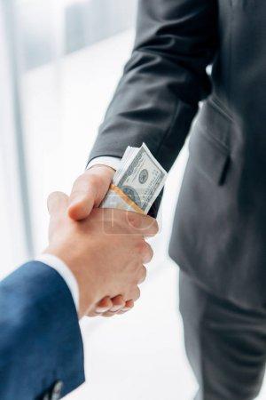 Photo pour Vue recadrée de l'homme donnant le pot-de-vin à l'associé d'affaires et se serrant la main dans le bureau - image libre de droit