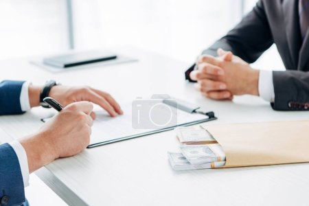 Photo for Selective focus of businessman signing document near envelope with bribe and business partner - Royalty Free Image