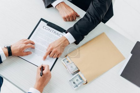 Photo for Cropped view of man signing contract near business partner pointing with finger - Royalty Free Image