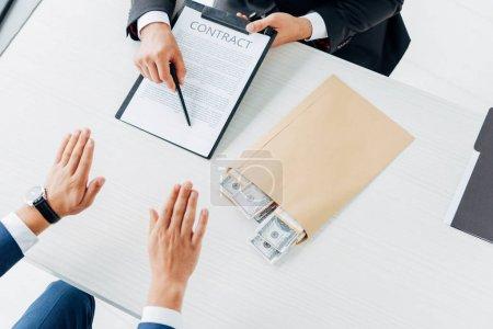 Photo pour Vue recadrée de l'homme faisant des gestes près du stylo de fixation de partenaire d'affaires et du contrat - image libre de droit