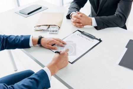 Photo pour Foyer sélectif de l'homme d'affaires signant document près de l'enveloppe avec pot-de-vin et partenaire d'affaires avec les mains serrées - image libre de droit