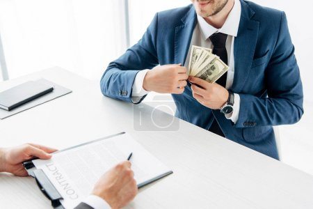 Photo for Cropped view of man holding pen near contract and business partner putting bribe in pocket - Royalty Free Image