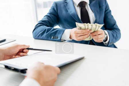 cropped view of man holding clipboard and pen near business partner holding money