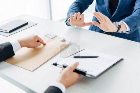 Photo pour Foyer sélectif de l'homme tenant presse-papiers et pointant avec le doigt au contrat avec stylo près partenaire d'affaires gestuelle dans le bureau - image libre de droit