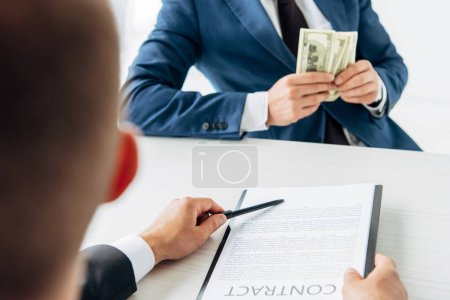 Photo pour Foyer sélectif de l'homme tenant le presse-papiers et le contrat avec le stylo près du partenaire d'affaires retenant l'argent - image libre de droit