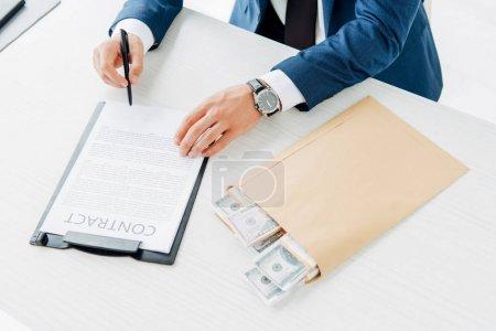 Photo pour Vue supérieure de stylo de fixation d'homme d'affaires tout en signant le contrat près de l'enveloppe avec l'argent sur la table - image libre de droit