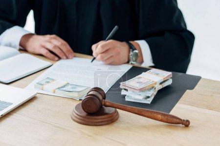 Photo pour Vue recadrée du juge signant le document près de l'argent et le marteau - image libre de droit