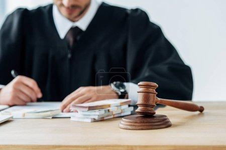 Photo pour Mise au point sélective de marteau en bois près de l'écriture juge dans le bureau - image libre de droit