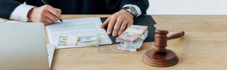 Photo pour Panoramique coup de marteau en bois près juge écriture près de l'argent dans le bureau - image libre de droit