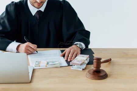 Photo pour Vue raccourcie du juge retenant le stylo près des documents et du marteau en bois sur la table - image libre de droit