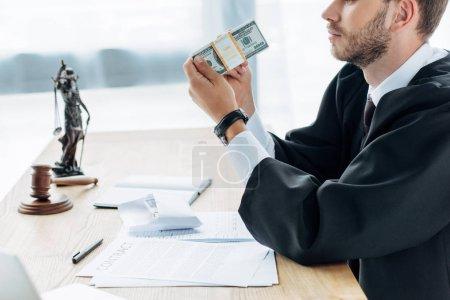 Photo pour Vue recadrée du juge détenant l'argent et l'enveloppe près du contrat - image libre de droit