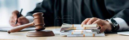 Photo pour Plan panoramique du juge touchant l'argent près du marteau en bois - image libre de droit