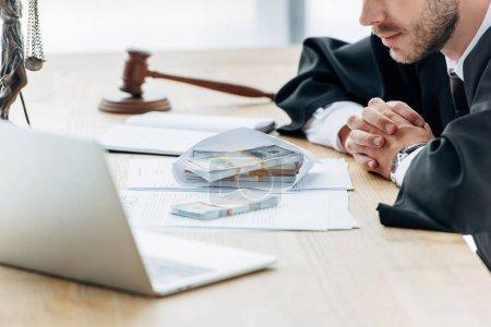 Photo pour Vue recadrée du juge avec les mains serrées près de l'argent dans l'enveloppe et le marteau en bois - image libre de droit