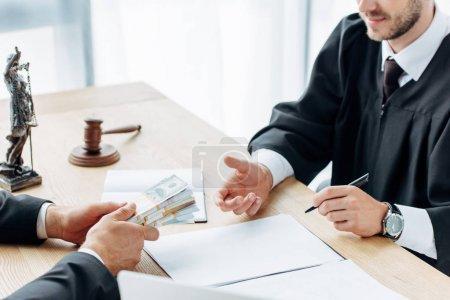 Photo pour Vue recadrée de l'homme donnant de l'argent pour juger assis près de la table - image libre de droit