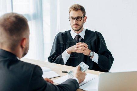 Photo pour Foyer sélectif de beau juge dans des lunettes assis avec les mains serrées et regardant l'homme tenant des billets en dollars - image libre de droit