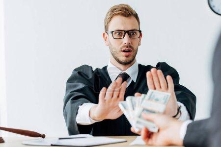 Photo pour Vue recadrée de l'homme tenant de l'argent près juge surpris dans des lunettes geste dans le bureau - image libre de droit
