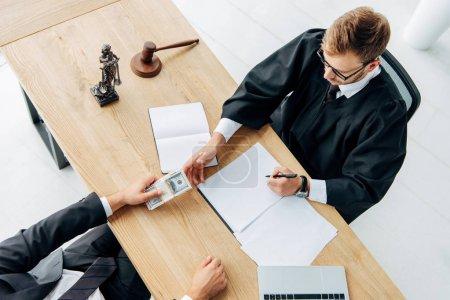 Photo pour Vue supérieure de l'homme donnant l'argent comptant au juge s'asseyant dans le bureau - image libre de droit