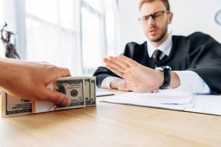 Photo pour Foyer sélectif de l'homme tenant de l'argent près du juge gestuelle dans le bureau - image libre de droit
