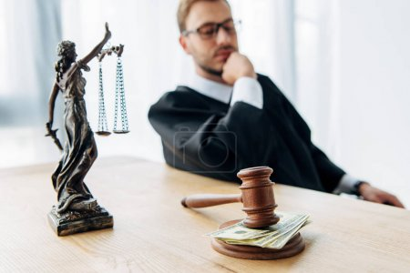 Photo pour Focalisation sélective du marteau et de la statuette de justice près du juge regardant les billets en dollars - image libre de droit