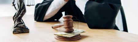 Photo pour Tir panoramique du juge près du marteau en bois avec de l'argent sur la table - image libre de droit