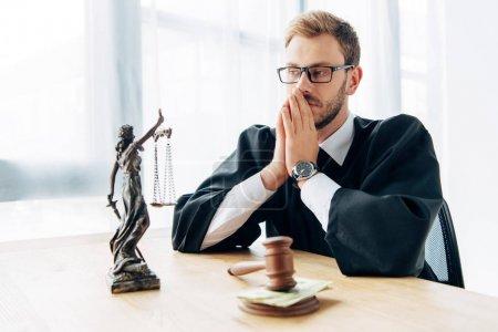 Photo pour Foyer sélectif du juge dans des lunettes couvrant visage près du marteau en bois avec de l'argent et statuette de justice - image libre de droit