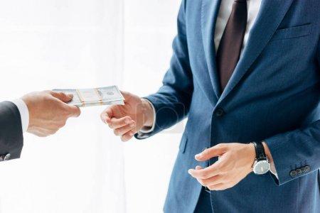 Photo pour Vue recadrée de l'homme donnant le pot-de-vin à l'associé d'affaires sur le blanc - image libre de droit