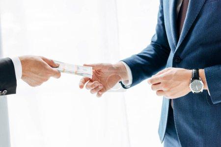 Photo pour Vue recadrée de l'homme d'affaires donnant pot de vin à un partenaire d'affaires sur blanc - image libre de droit