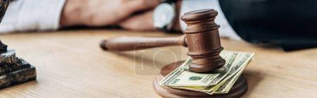 Photo pour Coup panoramique de marteau en bois sur des billets de banque en dollars - image libre de droit