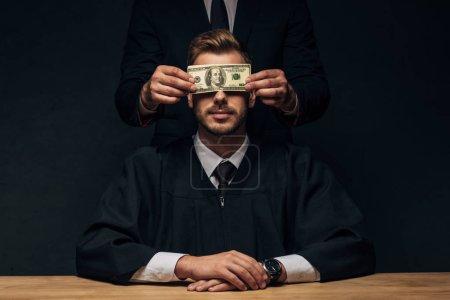 Photo pour Vue recadrée de l'homme restant et couvrant le visage du juge avec des billets de banque en dollars sur le noir - image libre de droit
