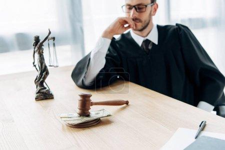 Photo pour Foyer sélectif de marteau avec pot de vin et statuette de justice près juge dans des lunettes - image libre de droit