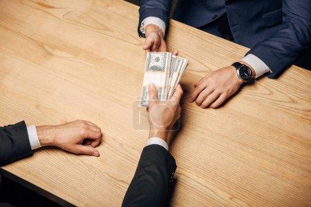 Photo pour Vue de dessus homme donnant pot de vin à un partenaire d'affaires près de la table en bois - image libre de droit