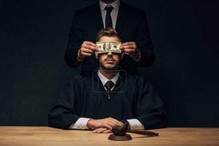 Photo pour Vue recadrée de l'homme couvrant le visage du juge avec l'argent sur le noir - image libre de droit
