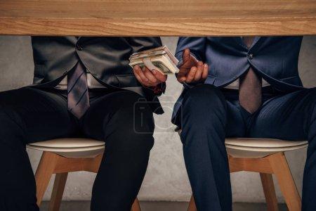 Photo pour Vue recadrée homme donnant de l'argent à partenaire d'affaires tout en étant assis sur la chaise - image libre de droit